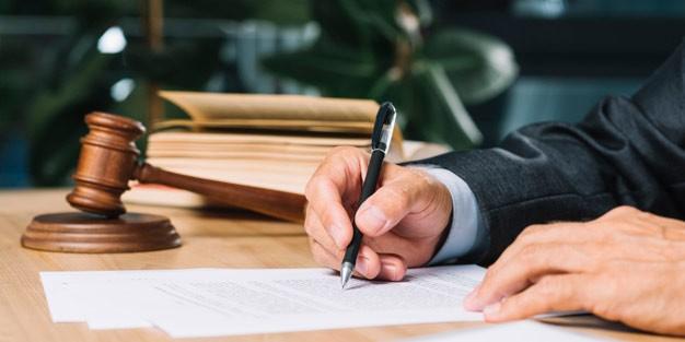 judge-holding-pen-checking-document-wooden-desk_23-2147898393