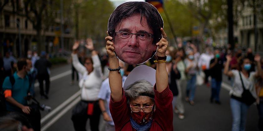Женщина держит портрет К. Пучдемона на демонстрации протеста у консульства Италии в Барселоне 24 сентября 2021